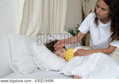 Caring Mom Check Small Sick Boy Temperature With Hand. Ill Kid With Flu Or Covid Illness Sleep In Be