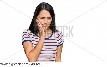 Young hispanic girl wearing casual striped t shirt touching mouth with hand with painful expression because of toothache or dental illness on teeth. dentist