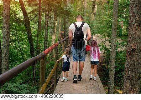 The Family Travels Along Ecological Hiking Trails In The Forest. A Girl With Pink African Pigtails A