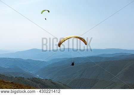 Paragliding In Mountains. Freedom To Fly In Air Over Mountains With Parachute. Paragliding Behind Bl