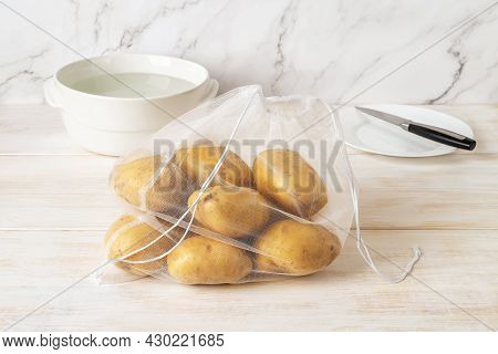 Raw Organic Potatoes In An Eco Reusable Mesh Bag On A White Wooden Table. Recycled Nylon Produce Bag