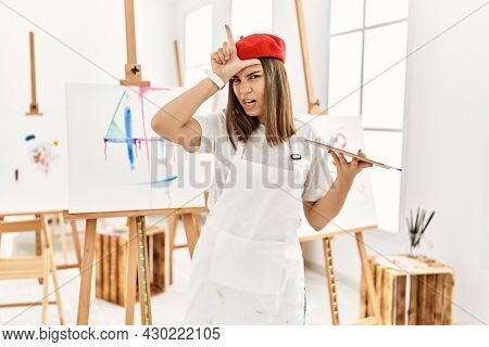 Young artist woman painting on a canvas at art studio making fun of people with fingers on forehead doing loser gesture mocking and insulting.