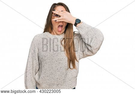 Young blonde woman wearing casual sweater and glasses peeking in shock covering face and eyes with hand, looking through fingers with embarrassed expression.