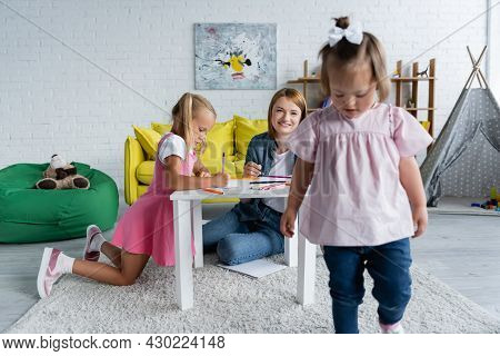 Smiling Kindergarten Teacher Looking At Blurred Kid With Down Syndrome Walking In Playroom