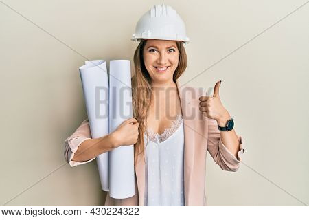 Young blonde woman wearing safety helmet holding blueprints smiling happy and positive, thumb up doing excellent and approval sign