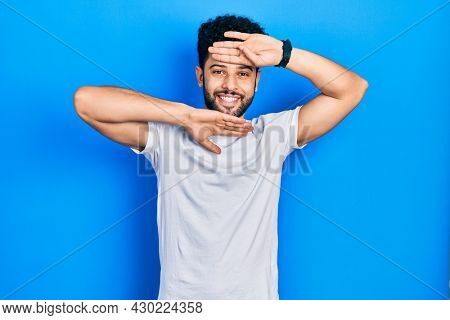Young arab man with beard wearing casual white t shirt smiling cheerful playing peek a boo with hands showing face. surprised and exited
