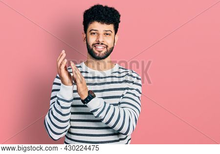 Young arab man with beard wearing casual striped sweater clapping and applauding happy and joyful, smiling proud hands together