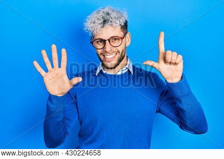 Young hispanic man with modern dyed hair wearing sweater and glasses showing and pointing up with fingers number seven while smiling confident and happy.