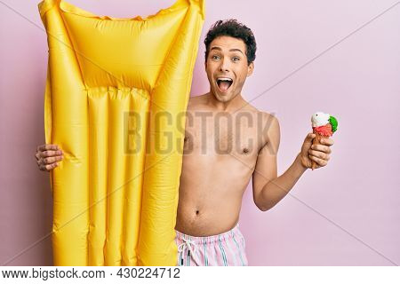 Young handsome man wearing swimsuit holding summer mattress float and icecream celebrating crazy and amazed for success with open eyes screaming excited.