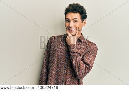 Handsome hispanic man wearing casual clothes looking confident at the camera smiling with crossed arms and hand raised on chin. thinking positive.