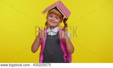 Smiling Cute Schoolgirl Wears Backpack, Reading Book, Making Playful Silly Facial Expressions And Gr