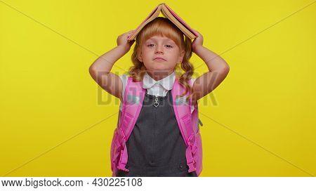 Cheerful Funny Teenage Schoolgirl Kid Dressed In Uniform Posing With Book On Head Looking Happy, Mak