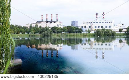 Sewage Pipe From A Metal Pipeline, Discharging Directly Into A Natural Pond With Green Grass On The