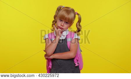 Thoughtful Clever Blond Teenage Girl Dressed In School Uniform Rubbing Her Chin And Looking Aside Wi
