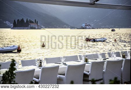 Empty Restaurant Tables Laid Out With Cutlery And Glasses And Chairs By The Waterside At Perast,mont