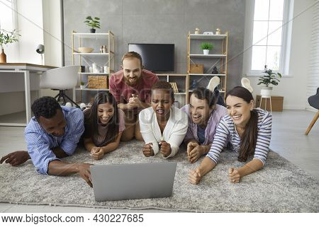 Group Of Multiracial Friends Have Fun Together At Home Watching An Interesting Movie Or Video.