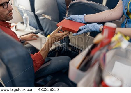 Close Up Shot Of Hands Of Male Passenger Getting Lunch Box From Female Flight Attendant Serving Food