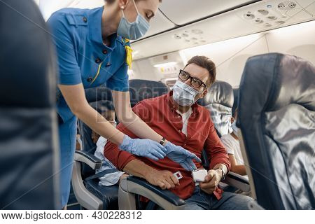 Man In Protective Face Mask Looking At Female Flight Attendant Helping Him To Adjust And Tight A Sea
