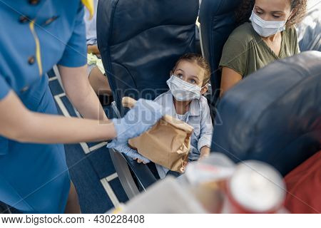 Cute Girl In Protective Face Mask Looking At Flight Attendant Serving Lunch To Little Passenger On B