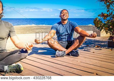 Young Happy Afro American Man Practicing Yoga By Seaside On Sunny Day With Friends, Enjoying Warmth