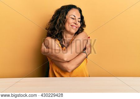 Beautiful middle age woman wearing casual clothes sitting on the table hugging oneself happy and positive, smiling confident. self love and self care