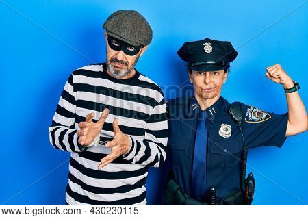 Middle age couple of hispanic woman and man wearing thief and police uniform strong person showing arm muscle, confident and proud of power