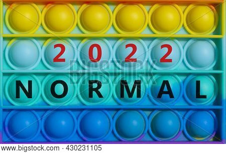Symbol Of Covid-19 Normal In 2022. Words 'normal 2022' On Rainbow Pop It. Beautiful Background, Copy