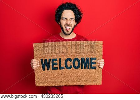 Handsome hispanic man holding welcome doormat sticking tongue out happy with funny expression.