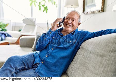 Senior man with grey hair sitting on the sofa at the living room of his house having a conversation speaking on the phone