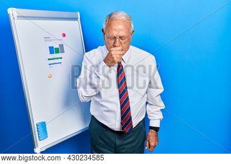 Senior man with grey hair standing by business blackboard feeling unwell and coughing as symptom for cold or bronchitis. health care concept.