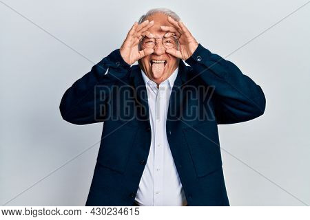 Senior man with grey hair wearing casual style and glasses doing ok gesture like binoculars sticking tongue out, eyes looking through fingers. crazy expression.