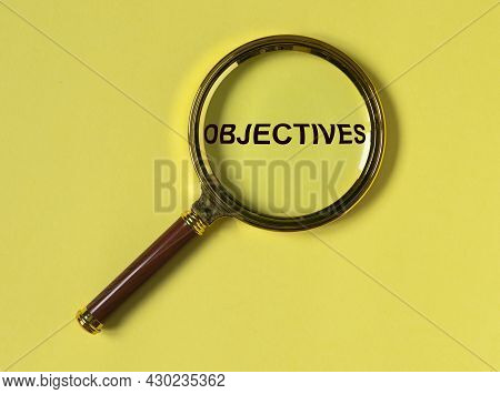 Word Objectives Through Magnifier On Yellow Background. Target Concept.