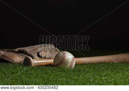 Old Baseball Bat And Mitt Low Angle Selective Focus On Grass Field And Dark Background
