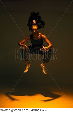 Dancing Mixed Race Girl Jumping And Levitating In Spotlight In Studio. Female Dancer Show Expressive