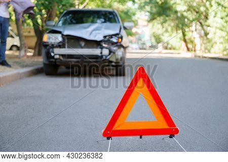 Red Triangle Warning Sign Of Car Accident On Road. Triangle In Front Of Wrecked Car In Summer Time.