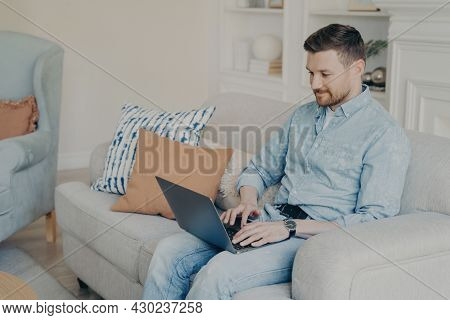 Relaxed Casually Dressed Young Businessman Working From Home While Sitting On Comfortable Couch In L