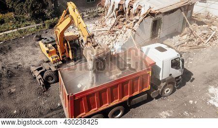 Excavator Bucket Loads Industrial Debris Into Truck. Process Of Demolishing And Destruction Old Hous