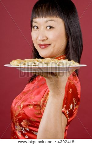 Chinese Woman Holding A Plate Full Of Dumplings