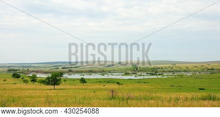 Panoramic Shot Of A Small Lake At The Foot Of A High Hill In The Steppe.