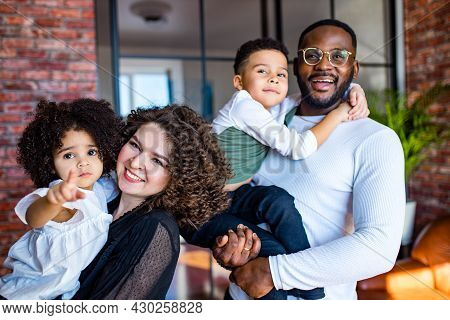 Afro American Mixed-raced Family Looking At Camera In Cozy Summer Day Light In Living Room