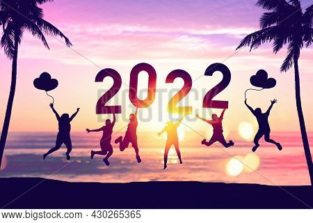 Silhouette Friends Jumping And Holding Number 2022 On Sunset Sky With Palm Tree Abstract Background