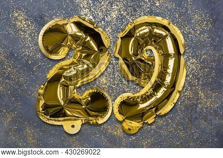 The Number Of The Balloon Made Of Golden Foil, The Number Twenty-nine On A Gray Background With Sequ