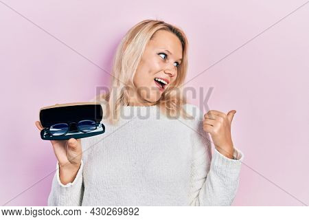 Beautiful caucasian blonde woman holding glasses in eyewear case pointing thumb up to the side smiling happy with open mouth