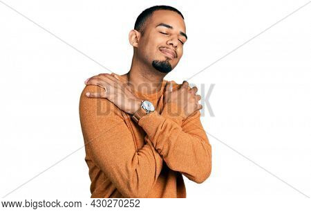 Young african american man wearing casual clothes hugging oneself happy and positive, smiling confident. self love and self care