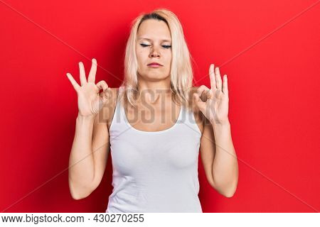 Beautiful caucasian blonde woman wearing casual white t shirt relax and smiling with eyes closed doing meditation gesture with fingers. yoga concept.