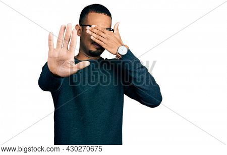 Young african american man wearing casual clothes and glasses covering eyes with hands and doing stop gesture with sad and fear expression. embarrassed and negative concept.