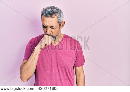 Handsome middle age man with grey hair wearing casual pink t shirt feeling unwell and coughing as symptom for cold or bronchitis. health care concept.