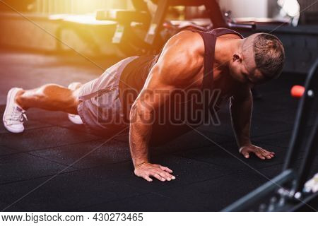 Sport Young Athletic Man Doing Push-up. Muscular And Strong Guy Exercising At A Gym.strength And Mot
