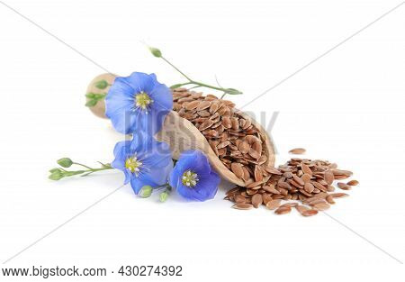 Wooden Scoop With Flax Flowers And Seeds On White Background