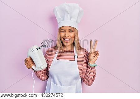 Beautiful hispanic woman holding pastry blender electric mixer smiling with happy face winking at the camera doing victory sign with fingers. number two.